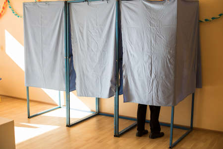 Color image of unidentifiable person voting in booths at a polling station, during elections.