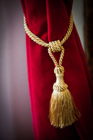 Image of a luxury red curtain and a cord.