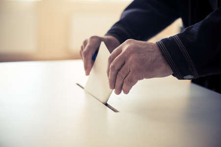 Color image of a person casting a ballot at a polling station, during elections. 스톡 콘텐츠