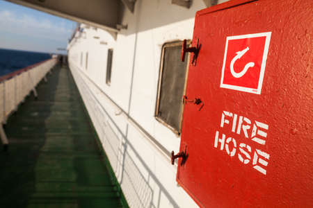 Color image of a red fire hose on a ship. 版權商用圖片