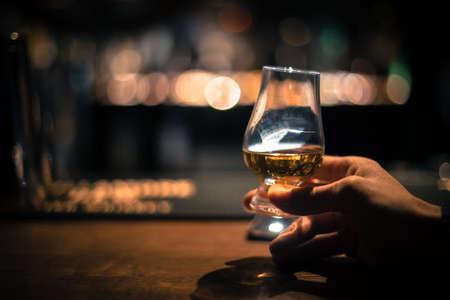 Primer plano de una mano sosteniendo un vaso de whisky de malta Glencairn. Foto de archivo
