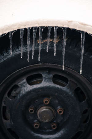 Close up shot of some icicles on a car's fender.