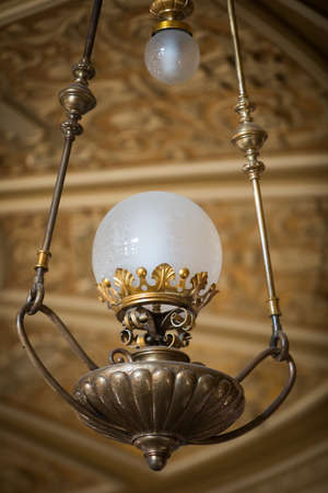 Color image of an old chandelier hanging from the ceiling, illuminated.