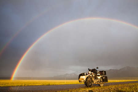 A sidecar motorcycle backed by a mountain range, under a rainbow. Banco de Imagens