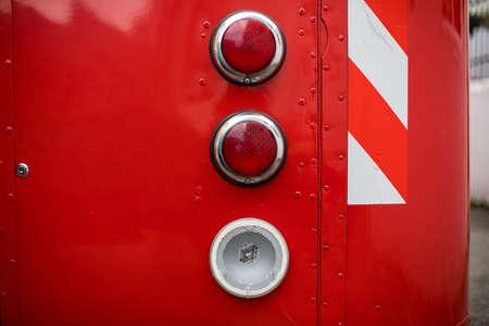 Close up shot of a vintage brake lights of a red bus.