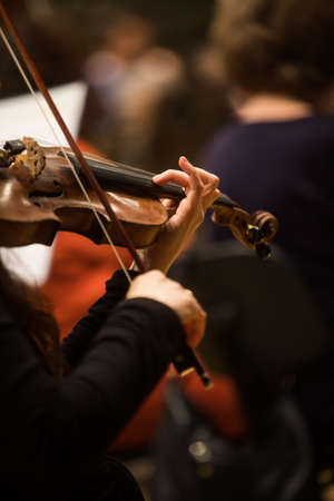 Close up shot of a woman performing on a violin during a concert. Banque d'images