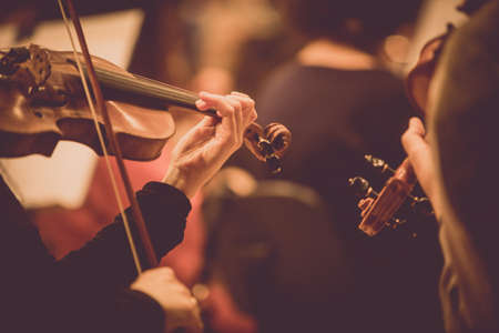 Close up shot of a woman performing on a violin during a concert. Stock Photo