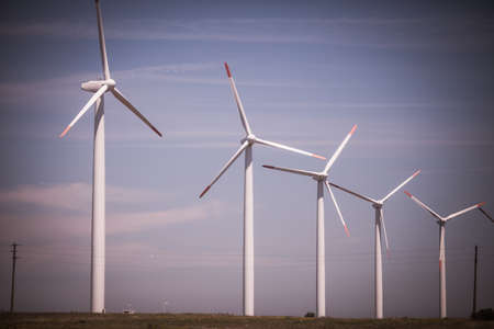 Color image of some wind mills on a meadow, against a blue sky.