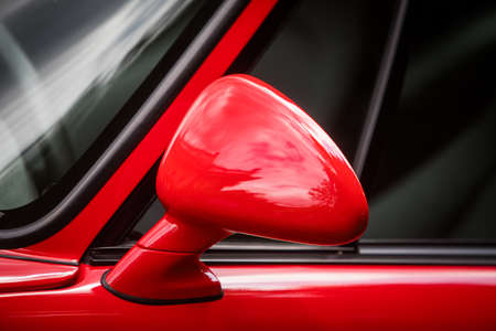 Close up shot of a red cars side mirror.