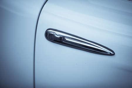 Close up shot of a vintage car door handle.