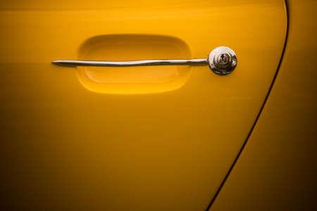 Close up shot of a vintage yellow car door handle. Banque d'images