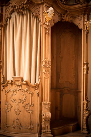 Image of a old wooden confessional in a church. Stock Photo