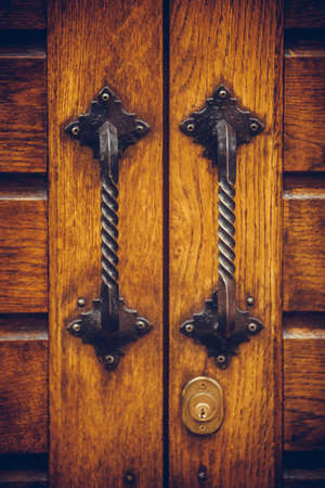 Color image of an old door handle on a wooden door. Archivio Fotografico