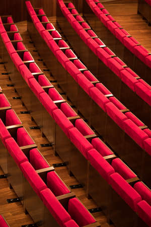 High angle image of rows of empty red seats in a conference room.