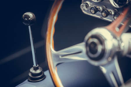 Close up horizontal shot of the gear shifter of a vintage car.