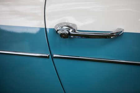 Close up shot of a vintage blue car door handle.
