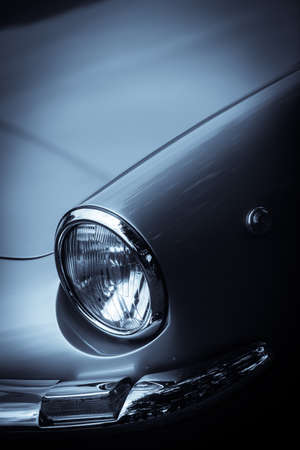 Close up vertical image of the headlight of a vintage classic car.