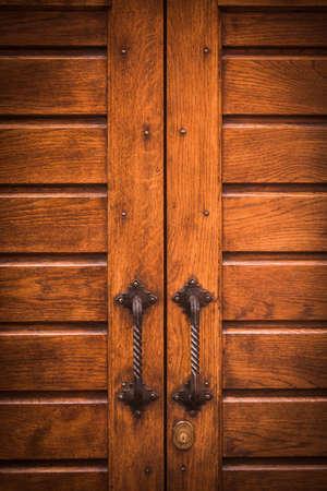 Color image of an old door handle on a wooden door. Stock fotó