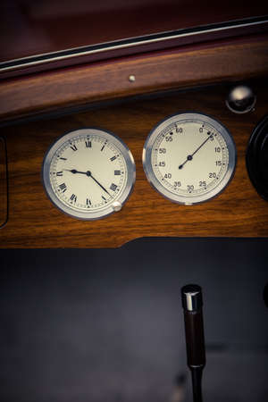 Color close up shot of a tachometer and a clock on a vintage cars dashboard.