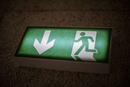 Color image of a green exit sign above a door.