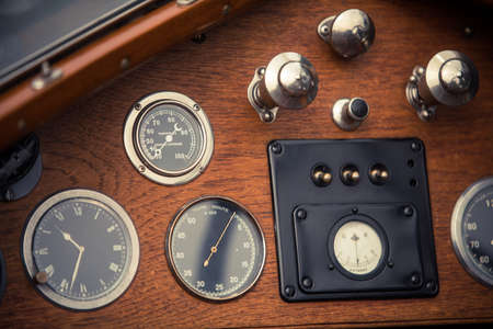 Color close up shot of a tachometer, a clock and a thermometer on a vintage cars dashboard. Stock Photo