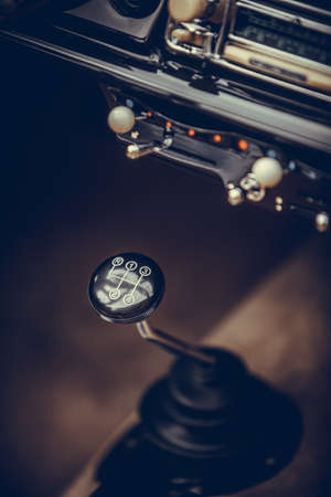 Close up vertical shot of the gear shifter of a vintage car.
