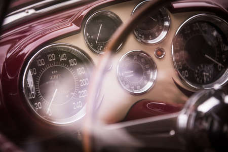 Color close up shot of a tachometer, a clock and other various gauges on a vintage cars dashboard. Stockfoto