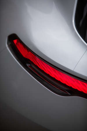 Close up vertical image of the LED tail lights of a new sport super car.