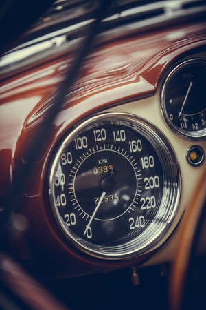 Color close up shot of a blue speedometer on a vintage cars dashboard.