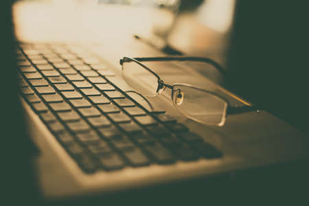Close up shot of a pair of glasses on a laptop keyboard, with shallow depth of field.