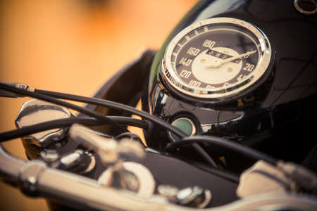 Close up horizontal image of the speedometer gauge of a vintage motorcycle.