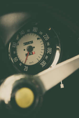 Color close up shot of a speedometer on a vintage cars dashboard.
