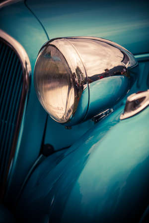 Close up vertical image of the headlight of a blue vintage classic car.