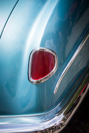 Close up vertical image of the red tail light of a blue classical vintage car.