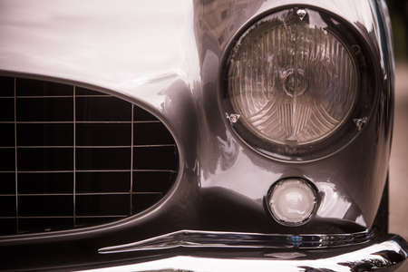 Close up horizontal image of the headlight of a vintage classic car.