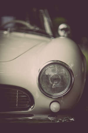 Close up vertical image of the headlight of a white vintage classic car.