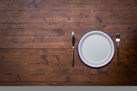Color image of an empty white plate with a fork and a knife on a wooden table, with copy space to the left. Banco de Imagens