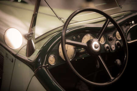 Color close up of the steering wheel and dashboard of an old classic car.