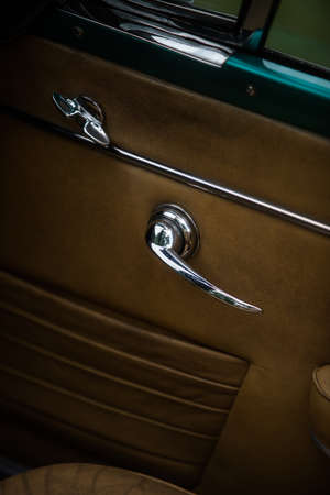 Close up shot of a vintage car door handle from the inside. Фото со стока