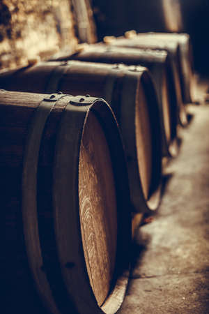 Close up shot of some wooden barrels in a dark wine cellar.