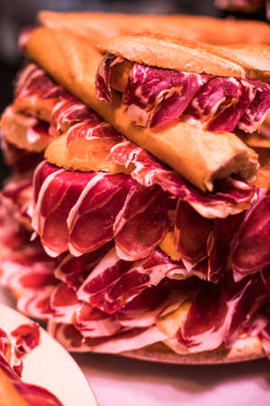 Close up shot of a pile of jamon sandwiches, a Spanish traditional dish.
