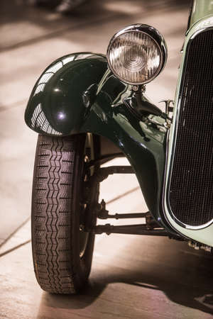 Close up vertical image of the headlight an wheel of a vintage classic car. Stock Photo