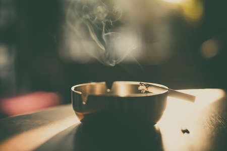 Close up shot of a burning cigarette in an ashtray, with smoke rising.
