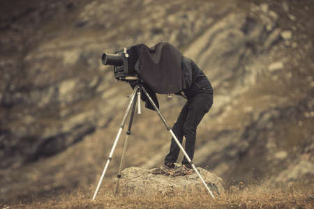 Close up shot of a photographer using a vintage camera on a tripod, backed by a mountain.