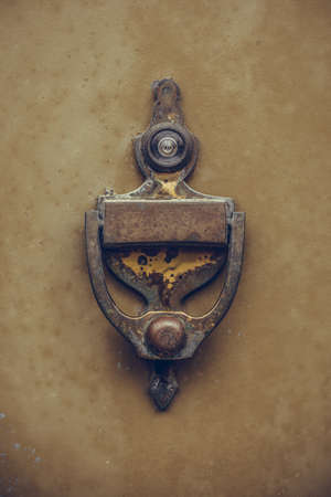 Color close up of a vintage door knocker on a wooden door.