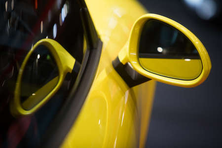 Close up shot of a yellow cars side mirror.