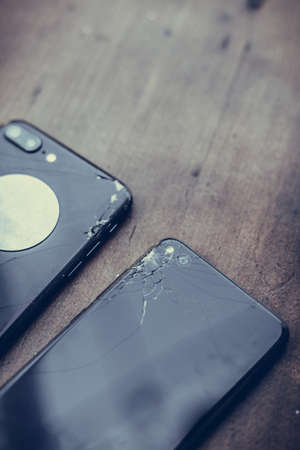 Close up shot of some mobile phones with broken screens on a wooden table. Reklamní fotografie