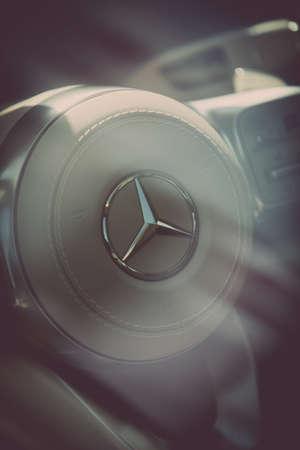 Bucharest, Romania - October 23, 2019: Illustrative editorial close up shot of the Mercedes Benz logo on a cars steering wheel. Mercedes is a German car manufacturer. Redakční