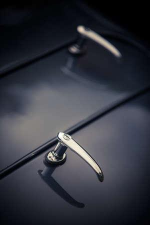 Close up shot of a vintage car trunk opener lever.