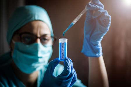 Conceptual image of a nurse using a pipette and a recipient with the coronavirus COVID-19 vaccine.